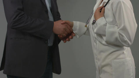 Grateful patient and doctor shake hands. Successful treatment Live Action