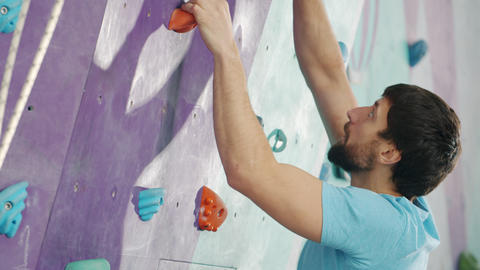 Attractive bearded guy climbing up the wall in rock-climbing gym enjoying Acción en vivo