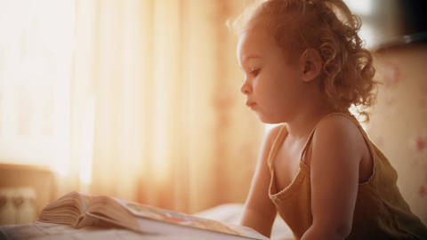 Peaceful baby girl looks at pictures in the book in sunny bedroom at home Acción en vivo