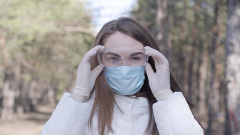 Young woman taking off protective eyeglasses and face mask and smiling at camera Live Action
