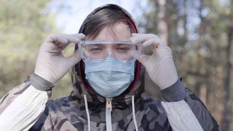 Close-up of young boy in face mask and gloves putting on protective eyeglasses Live Action