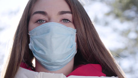 Close-up face of beautiful Caucasian girl in protective mask. Pretty brunette Live Action