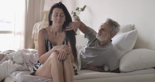 Handsome smiling Caucasian man touching wife's hair in the morning in bed Acción en vivo