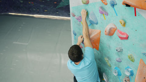 Slow motion of male climber pulling himself up on climbing wall in sports center Acción en vivo