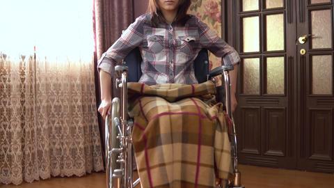 Young woman on a wheelchair. The girl moves in a wheelchair around the house Acción en vivo