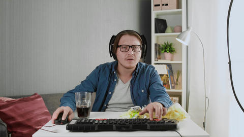 Pro Gamer in headphones Plays in the First Person Shooter on His Personal Live Action