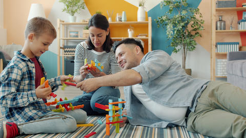 Child playing with mother and father at home building with construction blocks Acción en vivo