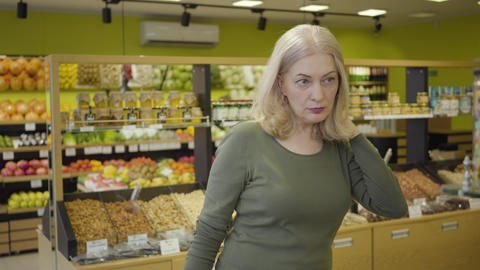Senior Caucasian blond woman choosing purchases in grocery. Portrait of Live Action