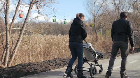 Young dad and mom are roller skating with the baby in a stroller, rear view Acción en vivo