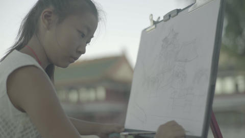The girl artist draws a drawing. Beijing. China Live Action
