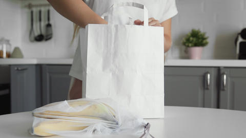 Close up of young woman unpacking paper shopping bag with fruits on the kitchen Acción en vivo