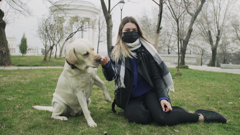 Woman sits on ground and plays with her labrador dog in the park during the Acción en vivo