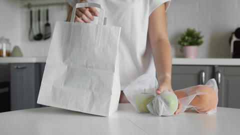 Close up of Young woman packing paper shopping bag with fruits on the kitchen on Acción en vivo