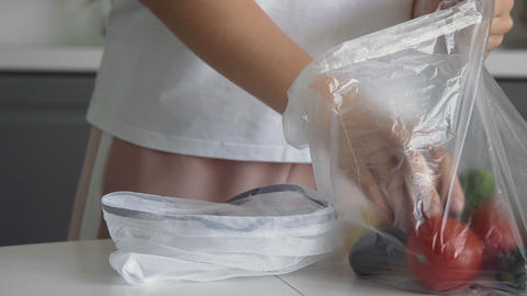 Close up of young woman move vegetables from plastic bag to reusable mesh bag on Live Action