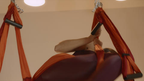 Gymnast doing backflip in hammock at studio.Woman performing aerial yoga indoors Live Action