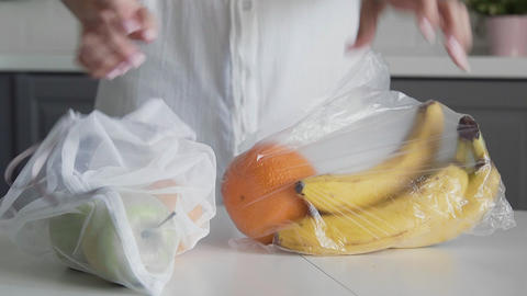 Young woman move fruits from plastic bag to reusable mesh bag on the kitchen Live Action
