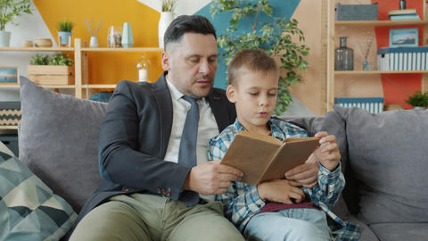 Father in formal clothing reading book to cheerful little boy in apartment Acción en vivo