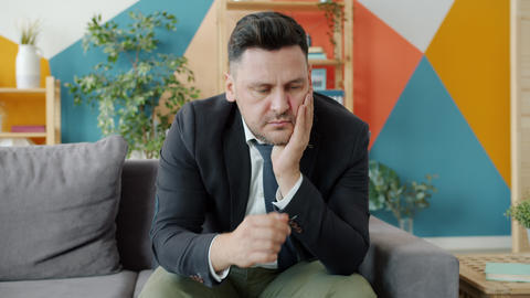 Unhappy entrepreneur thinking about problems touching face sitting on couch at Acción en vivo