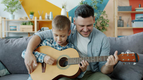 Happy family father and son playing the guitar in apartment having fun together Acción en vivo