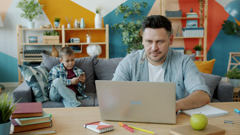 Middle aged man using laptop computer at home while son busy with smartphone Acción en vivo