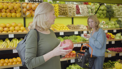Portrait of mature Caucasian woman advising with friend on purchase of juicy Live Action