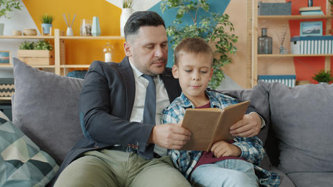 Dad businessman teaching little son to read holding book sitting on couch at Acción en vivo