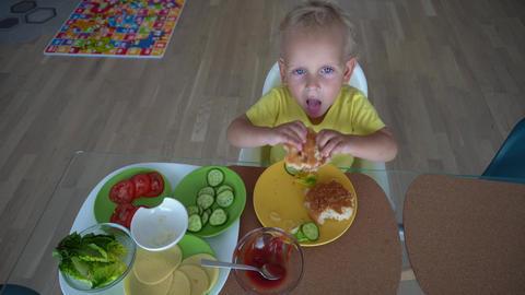 2 years old boy eating hamburger at home. Gimbal stabilizer motion top shot Acción en vivo