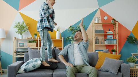 Active boy jumping on sofa having fun then doing high-five with joyful dad Acción en vivo