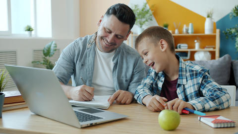 Young adult man drawing in notebook having fun with happy child at home Acción en vivo