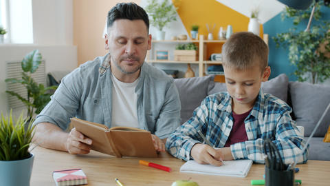 Father and son drawing pictures and reading books having fun indoors at home Live Action