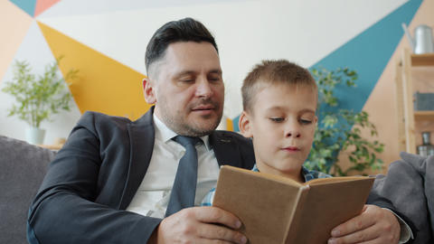 Man in suit and little kid are reading book in cozy apartment concentrated on Acción en vivo