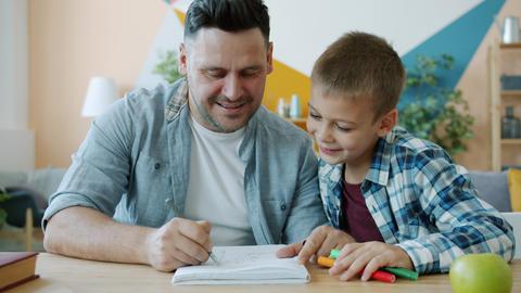Cheerful dad drawing funny pictures for happy child having fun at desk at home Acción en vivo