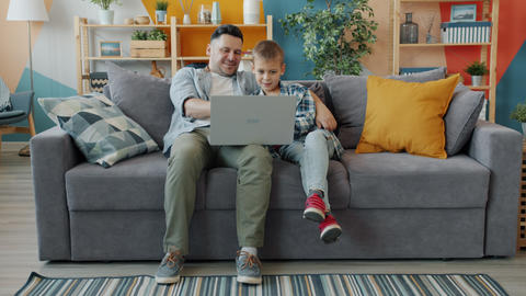 Little boy using computer with father sitting on couch in studio apartment Acción en vivo
