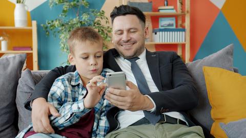 Businessman and little boy using smartphone enjoying online content at home Acción en vivo