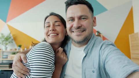 Portrait of happy husband and wife taking selfie at home hugging looking at Acción en vivo