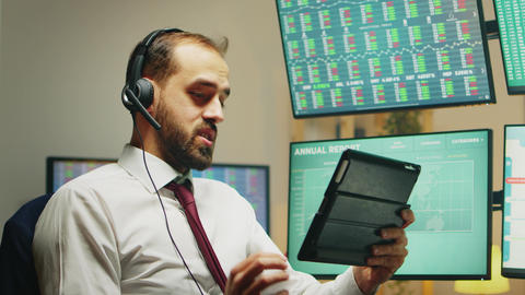 Stock market broker having a conversation on headphones while using tablet Live Action