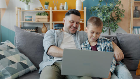 Dad and son using laptop typing smiling looking at screen sitting on sofa at Acción en vivo