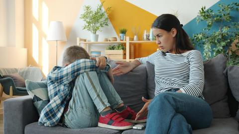 Strict woman punishing little son wagging finger at child sitting on sofa Live Action