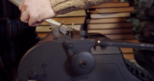 Close up of a retro writer putting paper into the typewriter, 4k Live Action