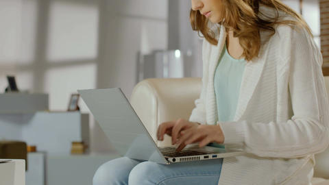 Female blogger typing actively on laptop, woman working at home Footage