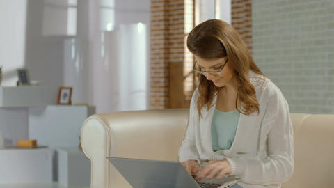 Young pretty girl in glasses chatting on laptop, smile at camera Footage