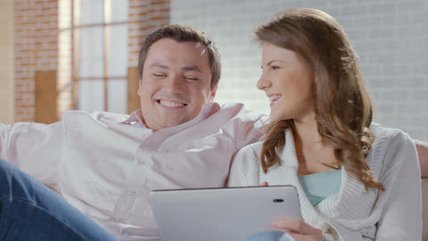Happy couple sitting on couch with tablet pc. Online shopping Footage