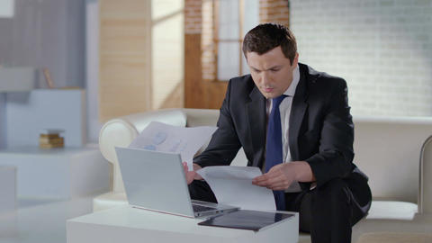 Businessman checking papers in office, web conference on laptop Footage