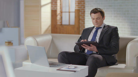 Handsome man business suit working on tablet, smiling at camera Footage