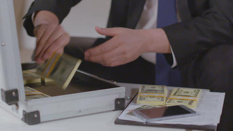 Businessman takes out dollar packs from briefcase, lots of money Footage