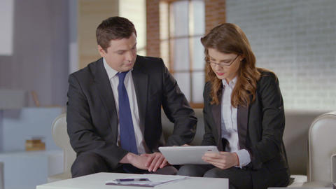 Female employee presenting report on tablet to boss, slow motion Footage