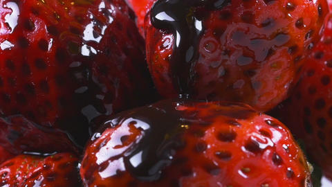 Delicious melted chocolate syrup pouring over strawberries Footage