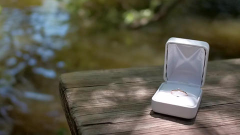 Gold engagement ring in white box sits on wooden table by river Live Action