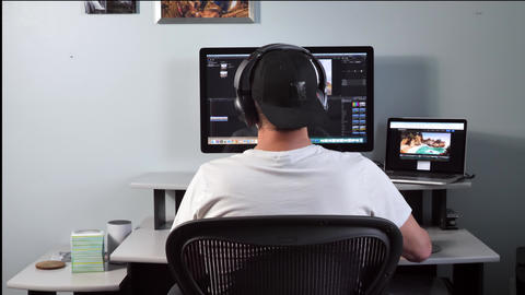 Male videographer editor working from home on computer, listening to music Live Action