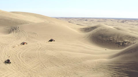 Aerial follow view, all terrain vehicles ATVs in desert driving over sand dunes Live Action